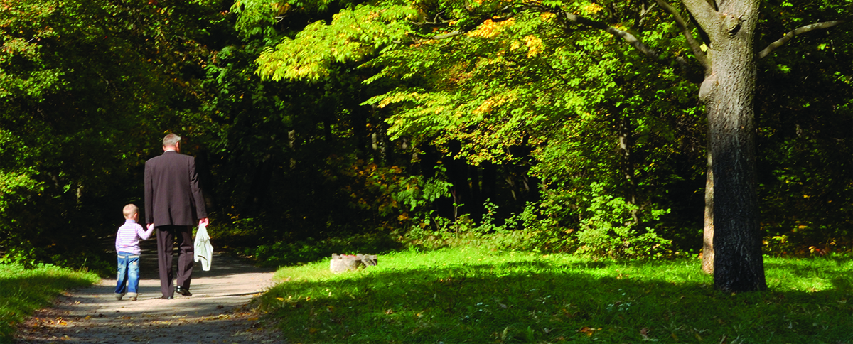 Grandfather with his grandson walking together through the autumn forest